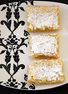 Lemon bars in a row on lovely serving dish