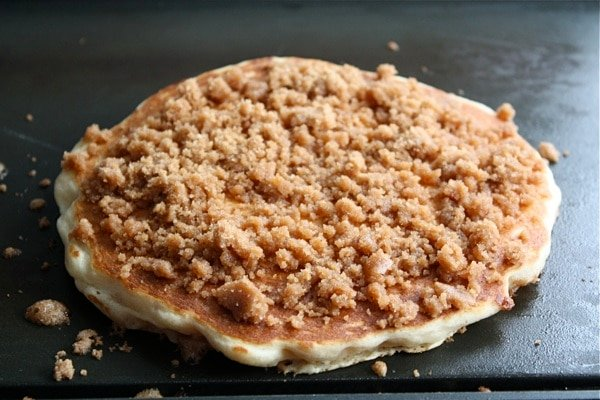 cooking cinnamon pancakes with streusel on top