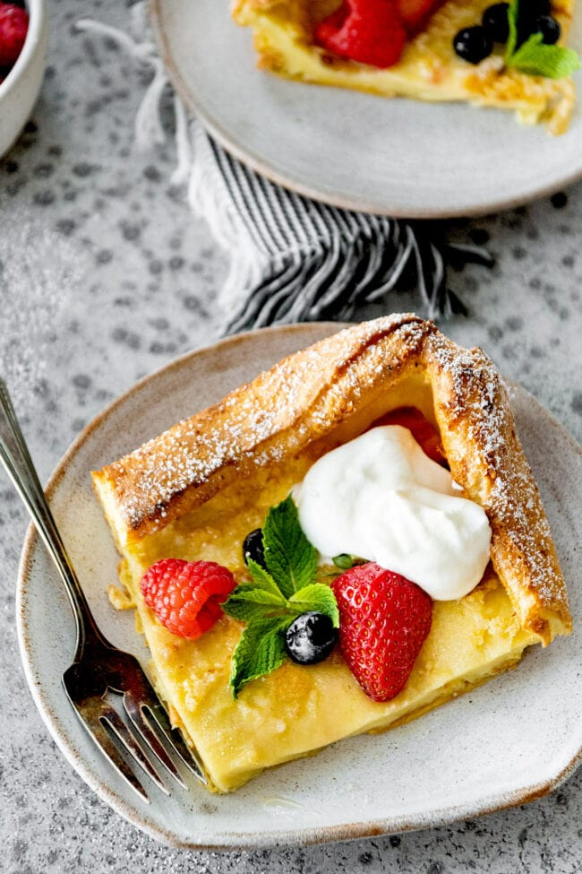 German pancakes on plate with berries and whipped cream