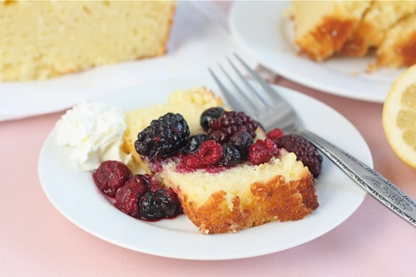 Lemon Ricotta Cake with berries and cream on plate