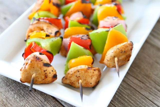 Three chicken kabobs with peppers served on platter
