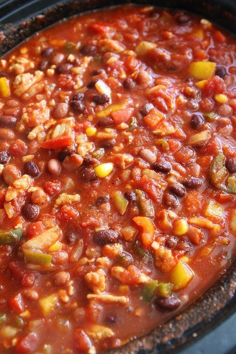 healthy turkey chili with beans and veggies cooking in crock pot