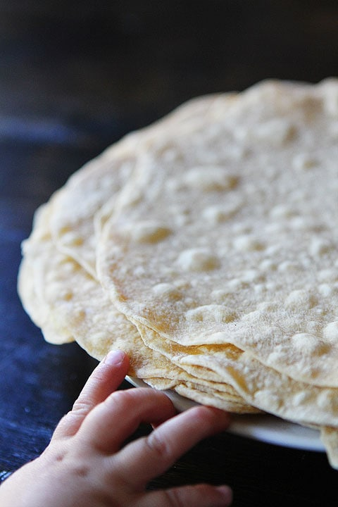 small hand reaching for plate of homemade flour tortillas