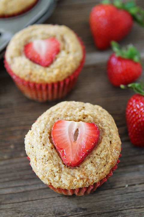 Whole Wheat Banana Muffins in red baking cups with strawberries on top