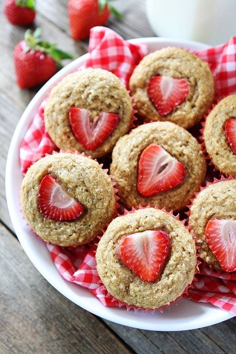 whole wheat banana muffins with strawberries on top piled in bowl
