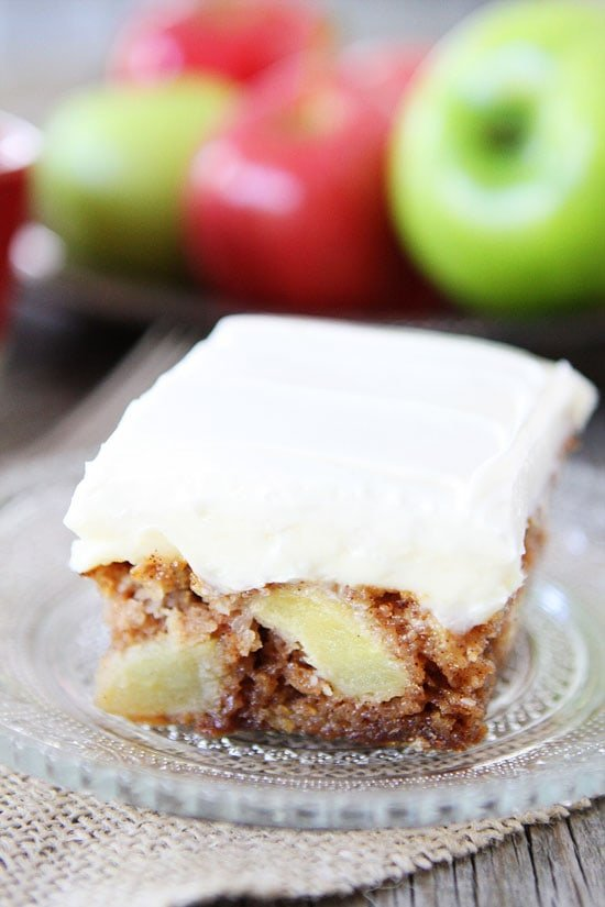 fresh apple cake with frosting on glass serving plate
