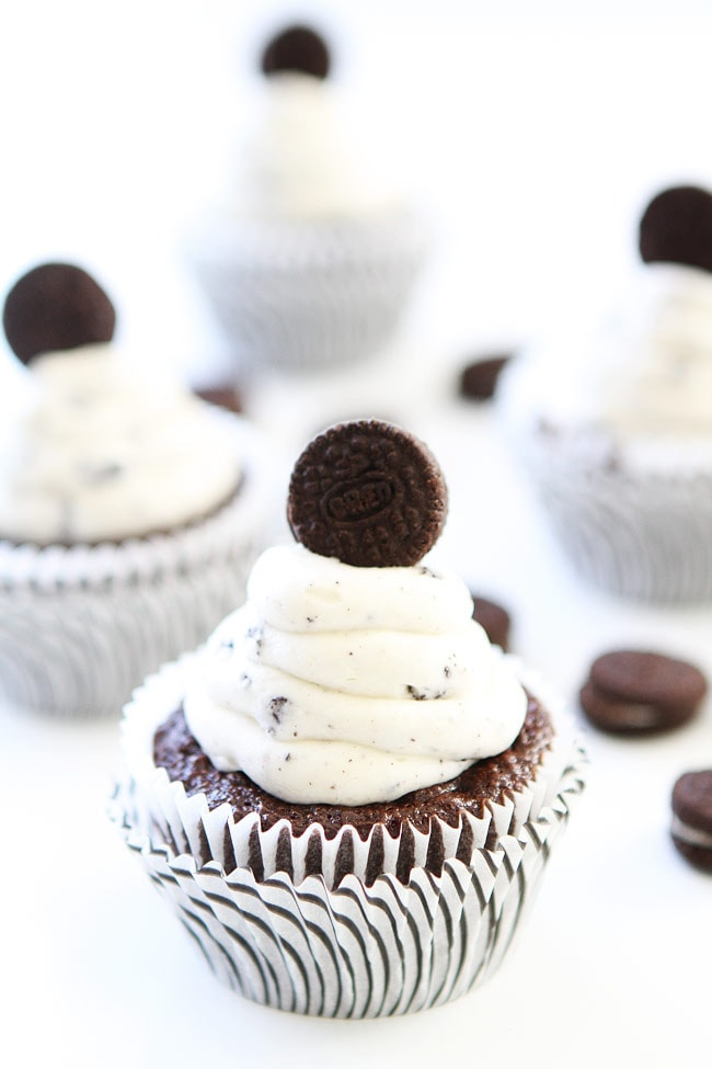 This is a triple layer chocolate cake with a cookies and cream filling, covered in a chocolate fudge frosting, topped with a white chocolate glaze and garnished with more Oreo cookies.