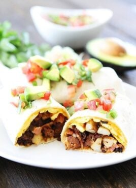 Breakfast burrito on plate topped with avocado and tomato
