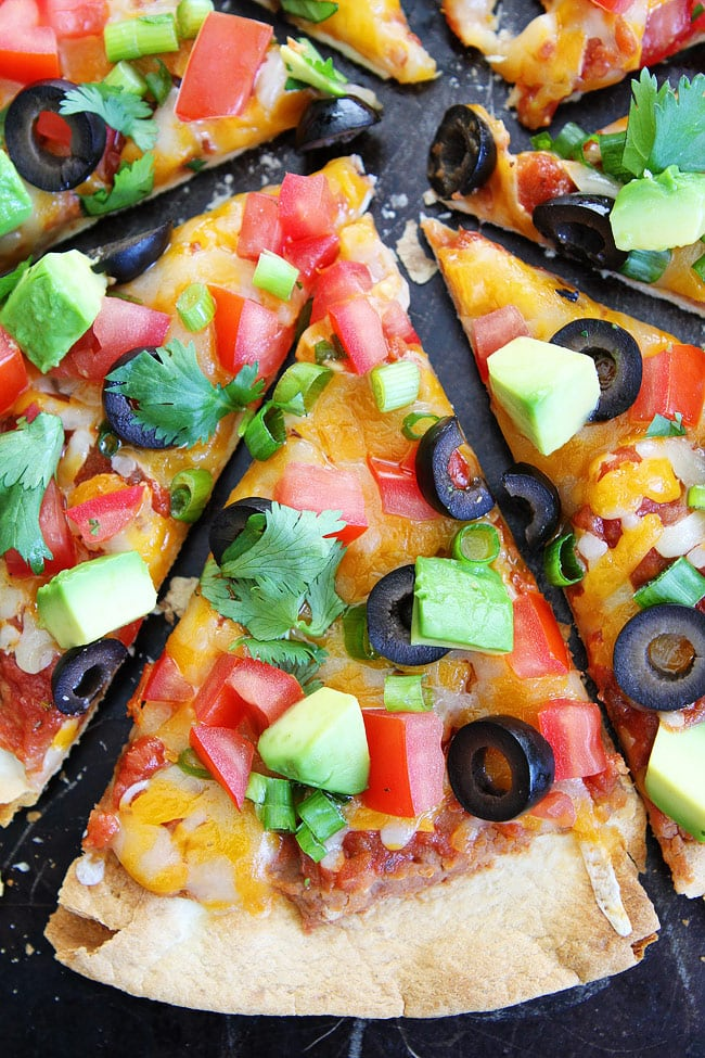 Mexican Pizza topped with cilantro, onions, avocado, tomatoes and olives