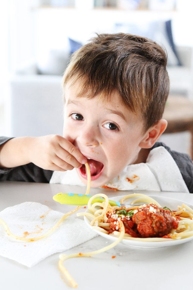 Kid slurping up spaghetti and meatballs