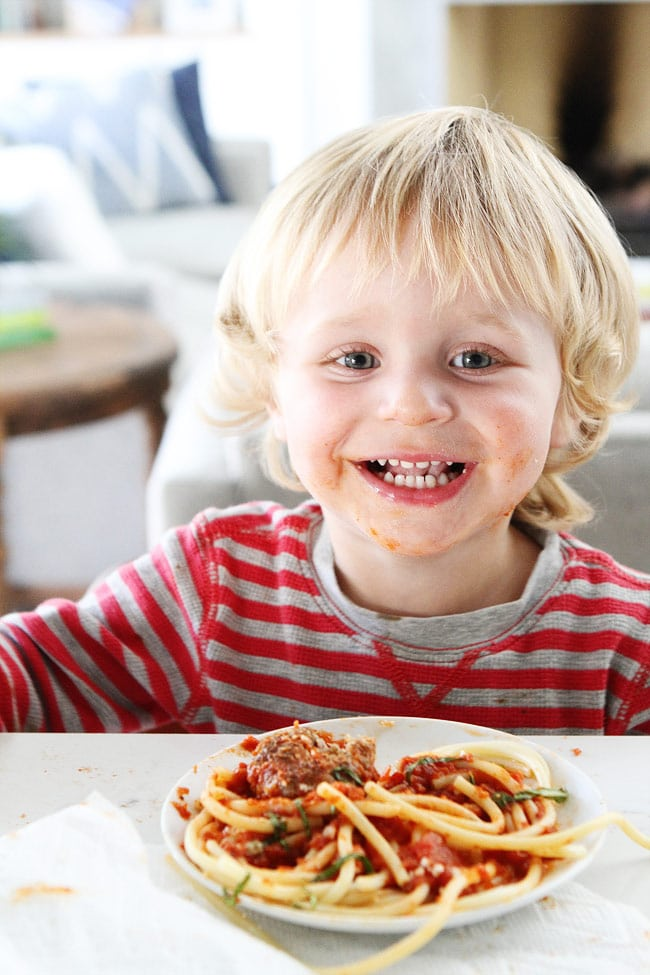 Smiling toddler with messy face eating spaghetti and meatballs