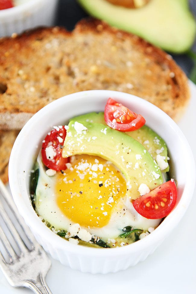 Ramekin of baked spinach and eggs with feta, avocado, and tomato