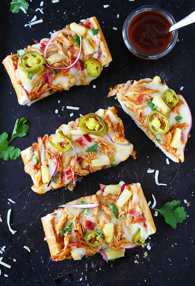BBQ Chicken French Bread Pizza made with store-bought French bread and topped with BBQ sauce, chicken, bacon, mozzarella cheese, pineapple, jalapeño, and cilantro. This easy pizza is a family favorite meal.