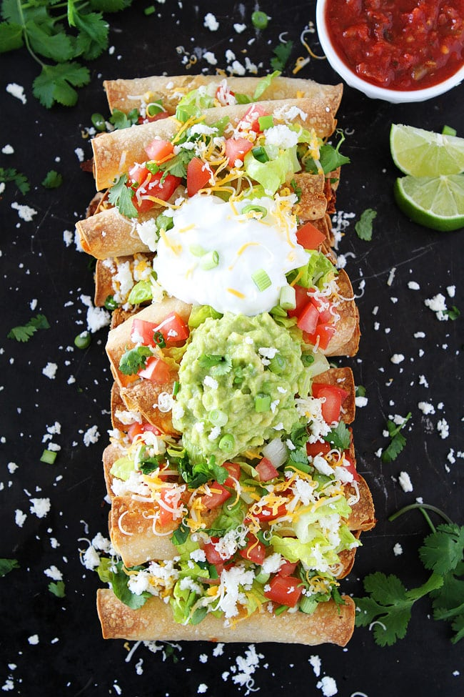 Baked Chicken Taquitos loaded with toppings on pan