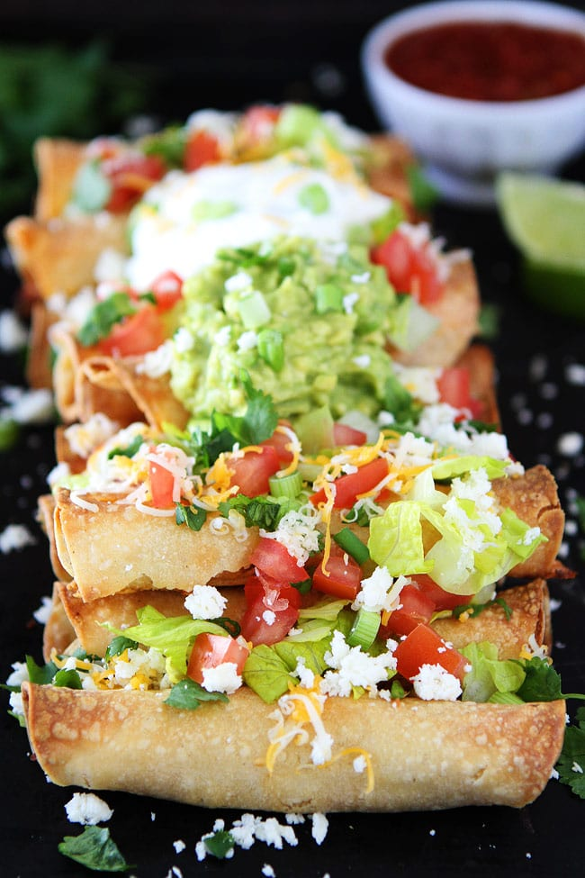 Homemade Taquitos topped with guacamole, cheese and tomato