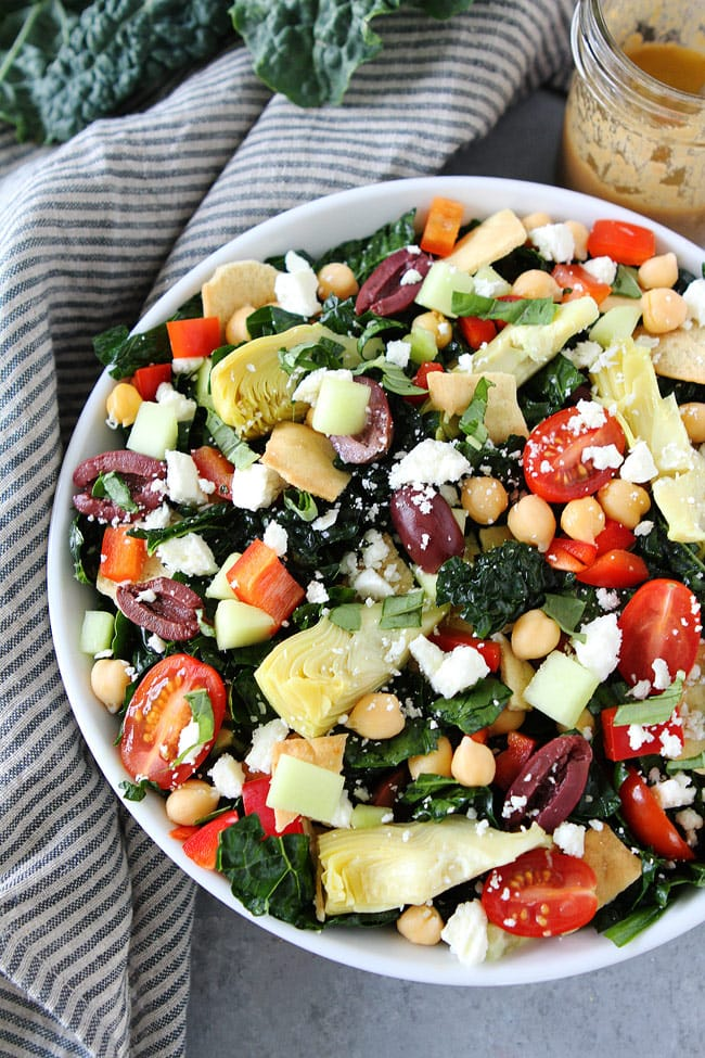 Mediterranean Kale Salad with chickpeas, tomatoes, cucumber, red pepper, artichoke hearts, olives, feta cheese, pita chips and a simple hummus dressing. This healthy salad is great as a main dish or side dish.