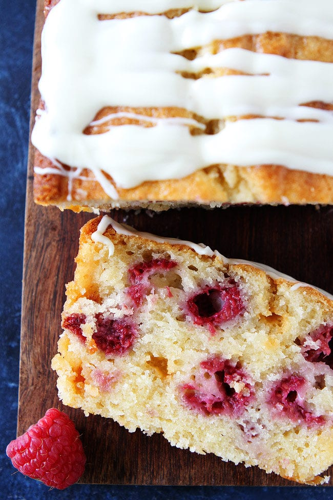Raspberry White Chocolate Loaf Cake with fresh raspberries, white chocolate chunks, and a sweet white chocolate glaze. An easy summer dessert!