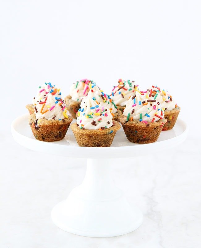 Sprinkle Chocolate Chip Cookie Cups topped with frosting are a fun dessert for any celebration. Kids and adults love these easy cookie cups!