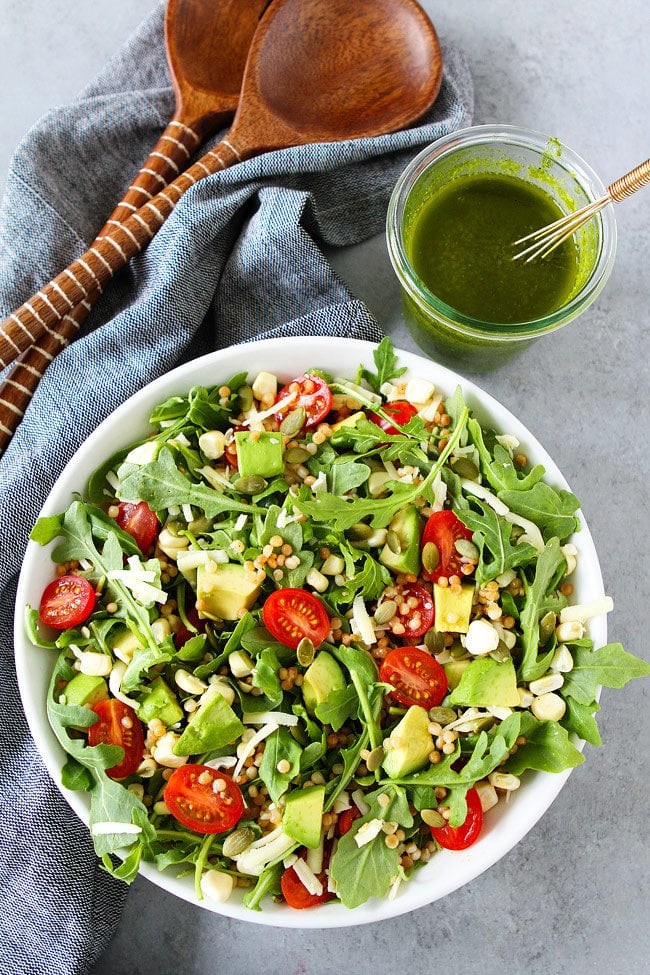 Summer Arugula Salad with couscous, avocado, corn, tomatoes, cheese, pepitas, and a simple basil vinaigrette. This fresh and easy salad is the best summer salad!