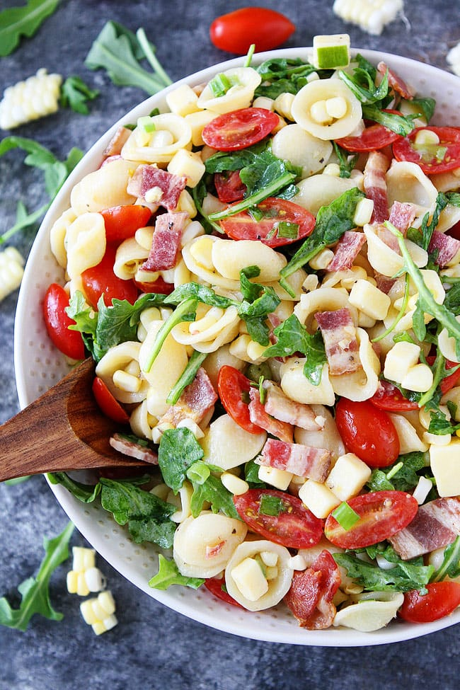 Easy Pasta Salad recipe with bacon, corn, tomatoes, cheese, and arugula. This pasta salad recipe is a family favorite!