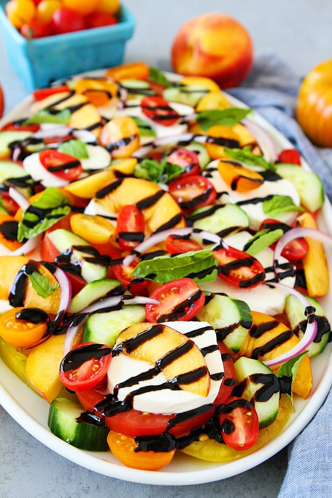 Summer Caprese Salad made with tomatoes, peaches, cucumber, fresh mozzarella cheese, red onion, basil, and a simple balsamic glaze. This easy summer salad is the BEST!