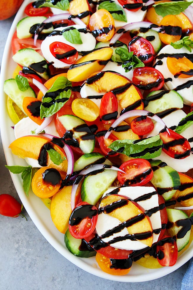 Summer Caprese Salad made with tomatoes, peaches, cucumber, fresh mozzarella cheese, red onion, basil, and a simple balsamic glaze. This easy summer salad takes minutes to make.