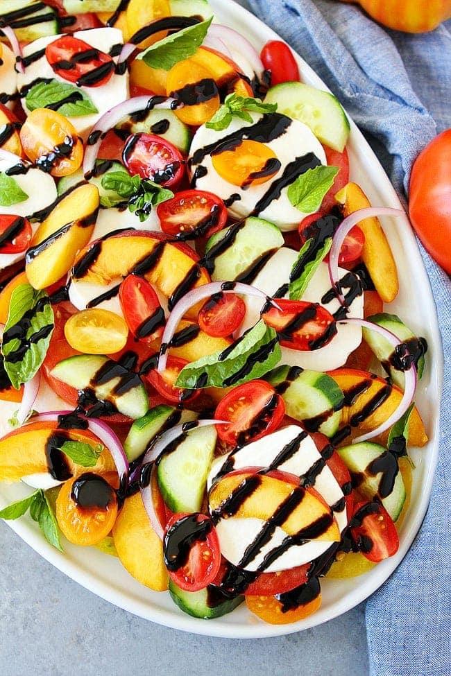 Summer caprese salad on platter with balsamic glaze