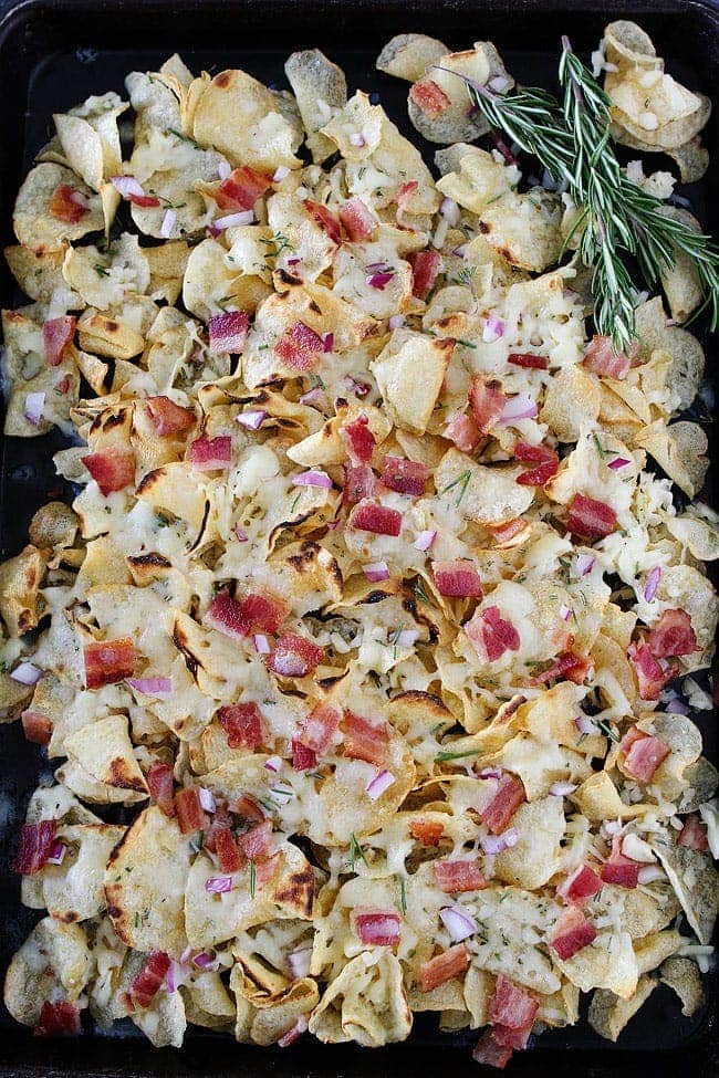 Kettle Chip Nachos with bacon, rosemary, white cheddar cheese, and red onion. These simple and gourmet nachos are the perfect party snack!
