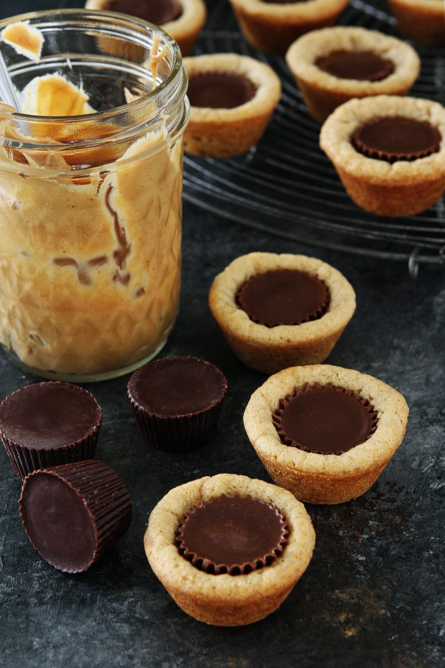 Peanut Butter Cup Cookies-peanut butter cookies made in mini muffin tins with a peanut butter cup in the center. These cookie cups are a family favorite and the perfect cookie for parties and the holidays! #peanutbutter #cookies #peanutbuttercups #holidays
