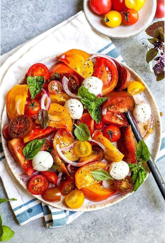 Tomato Salad on plate with mozzarella, basil, and onion
