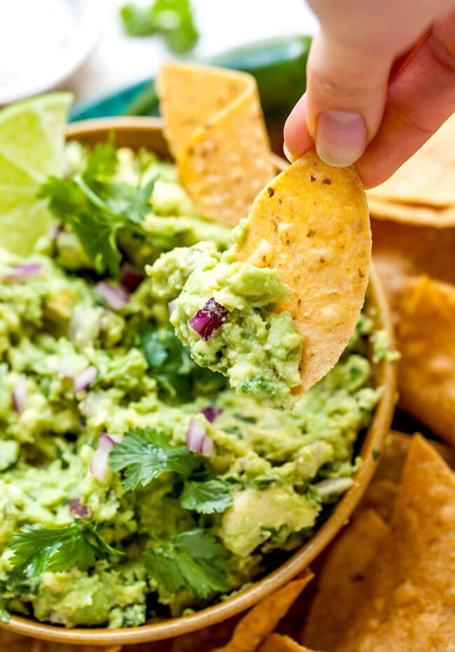 tortilla chip being dipped in guacamole