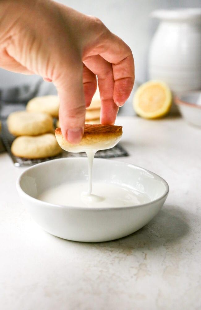 lemon cookies being dipped in lemon glaze