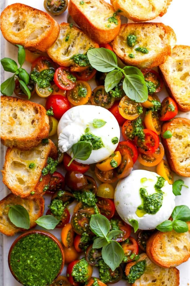 Burrata with tomatoes, pesto, and grilled bread on platter