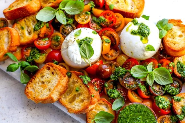 burrata with tomatoes, pesto, and grilled bread with fresh basil