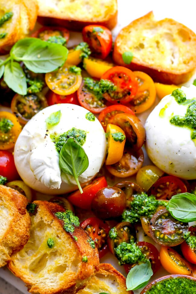 burrata with tomatoes, pesto, and grilled bread appetizer