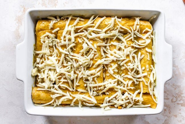 corn and zucchini enchiladas rolled in pan with shredded cheese