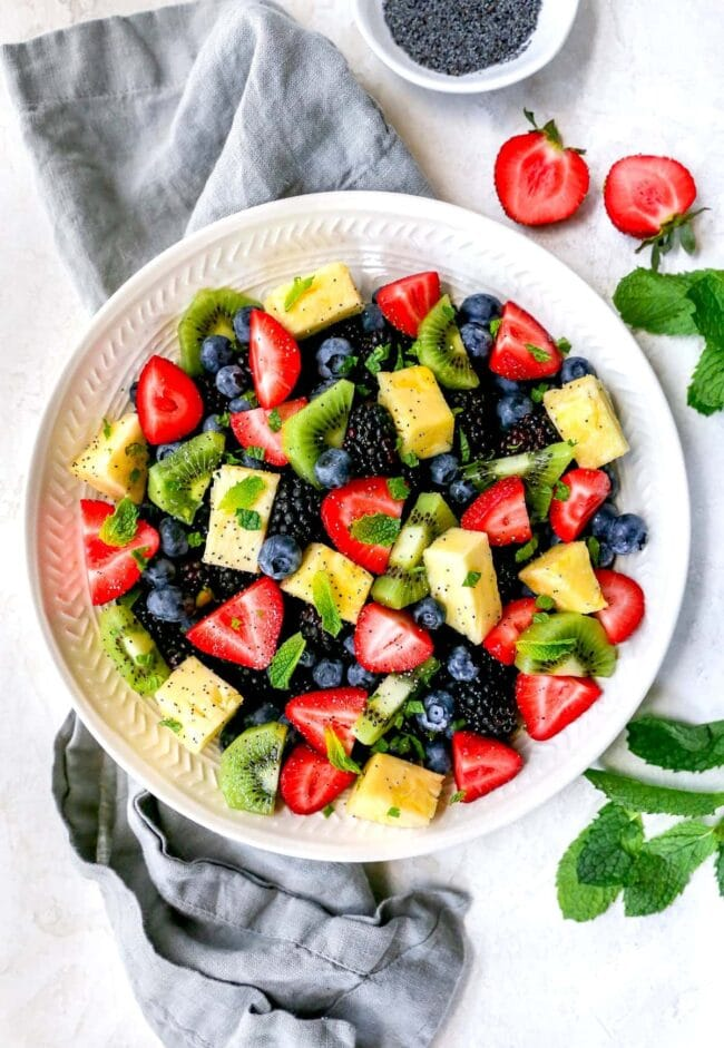 Fruit salad in bowl with citrus dressing and mint