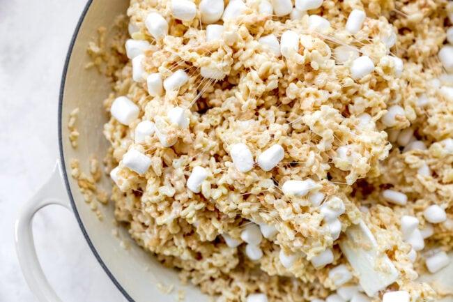 stirring rice krispie treats in pan