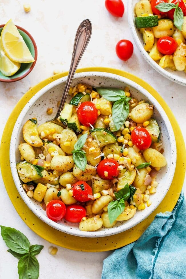 Butter Parmesan Gnocchi with squash, corn, and tomatoes in bowl with spoon