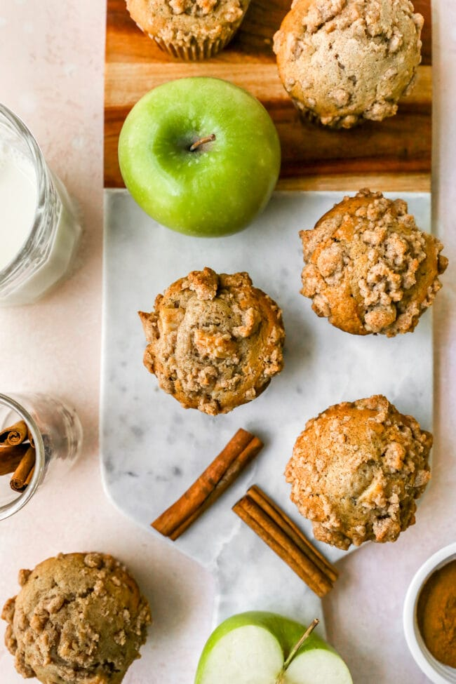 Apple Cinnamon Muffins with crumb topping on board with apple