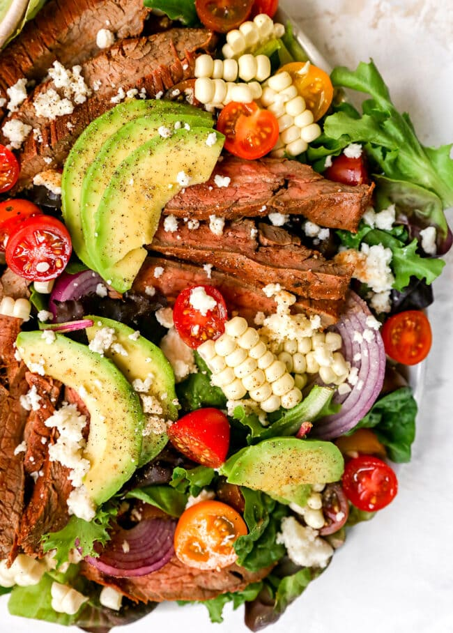 steak salad with avocados, tomatoes, and corn