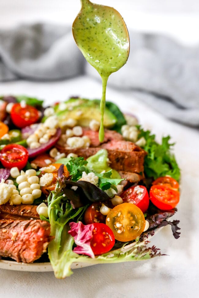 Drizzling dressing over steak salad