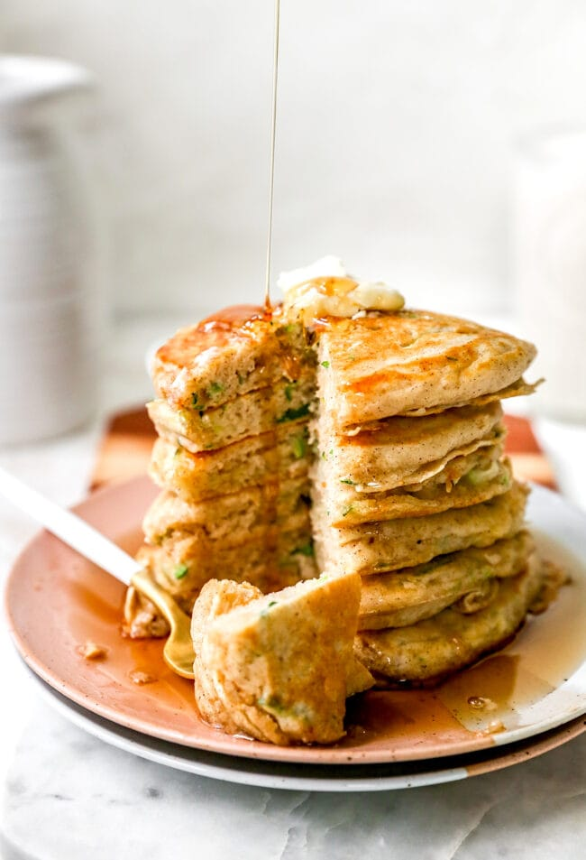 zucchini pancakes stacked and cut with maple syrup