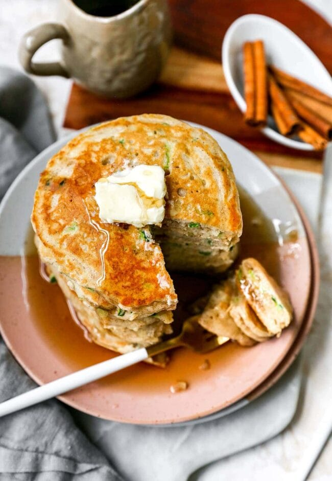 zucchini pancakes with butter and maple syrup on plate with fork