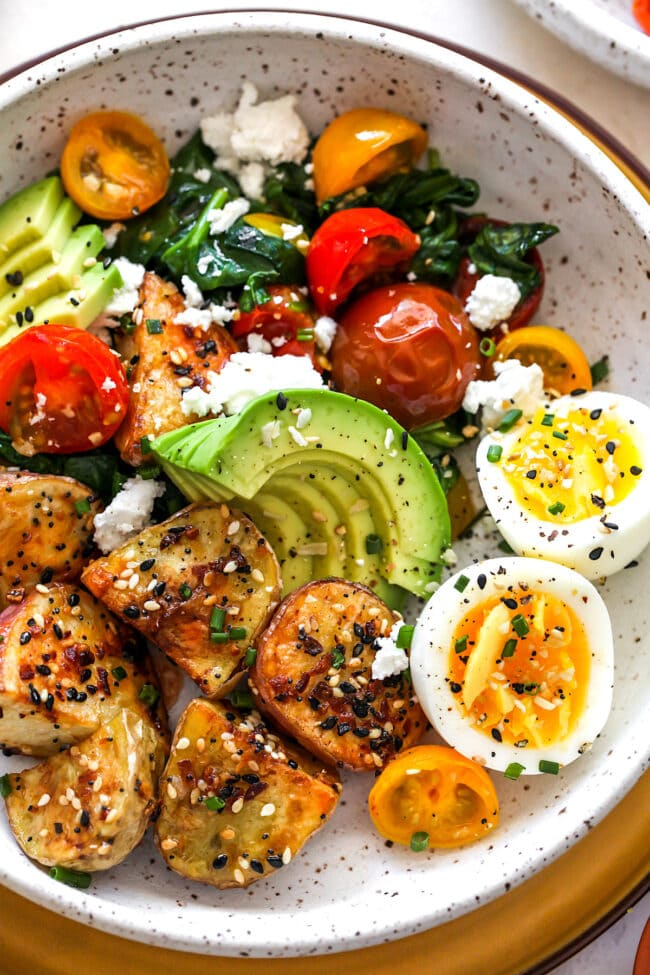 Savory Breakfast Bowl with potatoes, eggs, avocado, tomatoes, and spinach