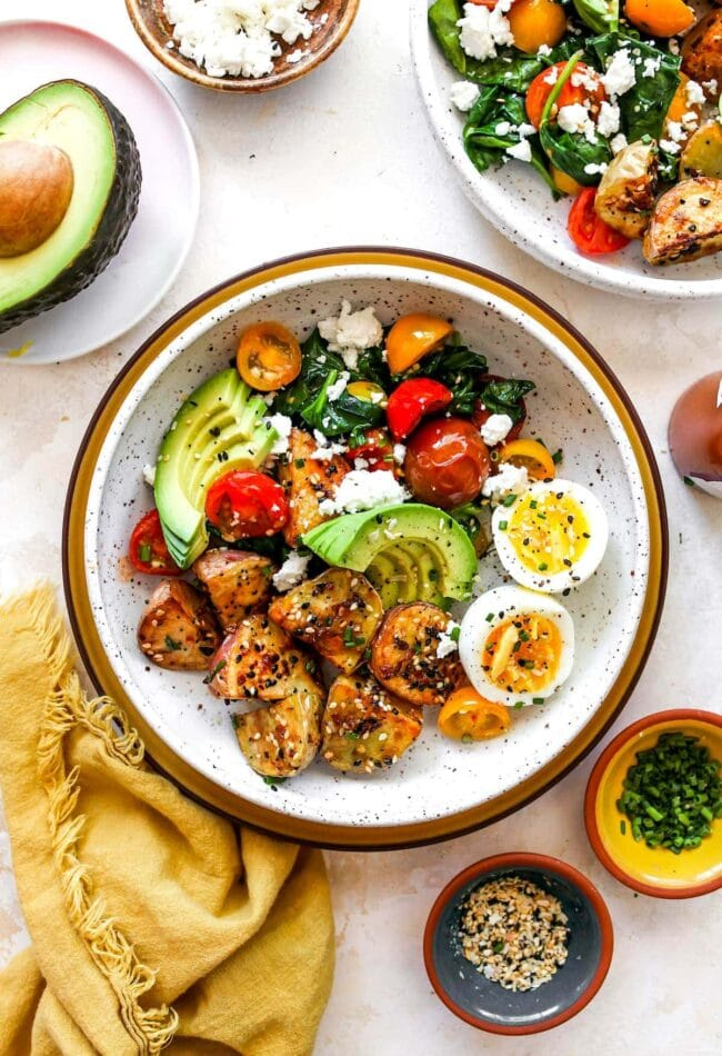 Healthy Savory Breakfast Bowl with eggs, potatoes, avocado, tomatoes, spinach, and cheese