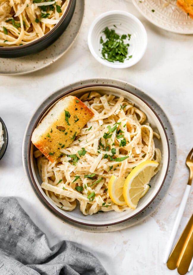 Fettuccine Alfredo in bowl with garlic bread