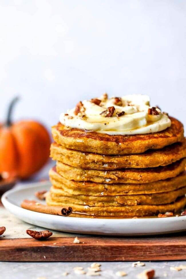 healthy pumpkin pancakes with whipped cream and maple syrup