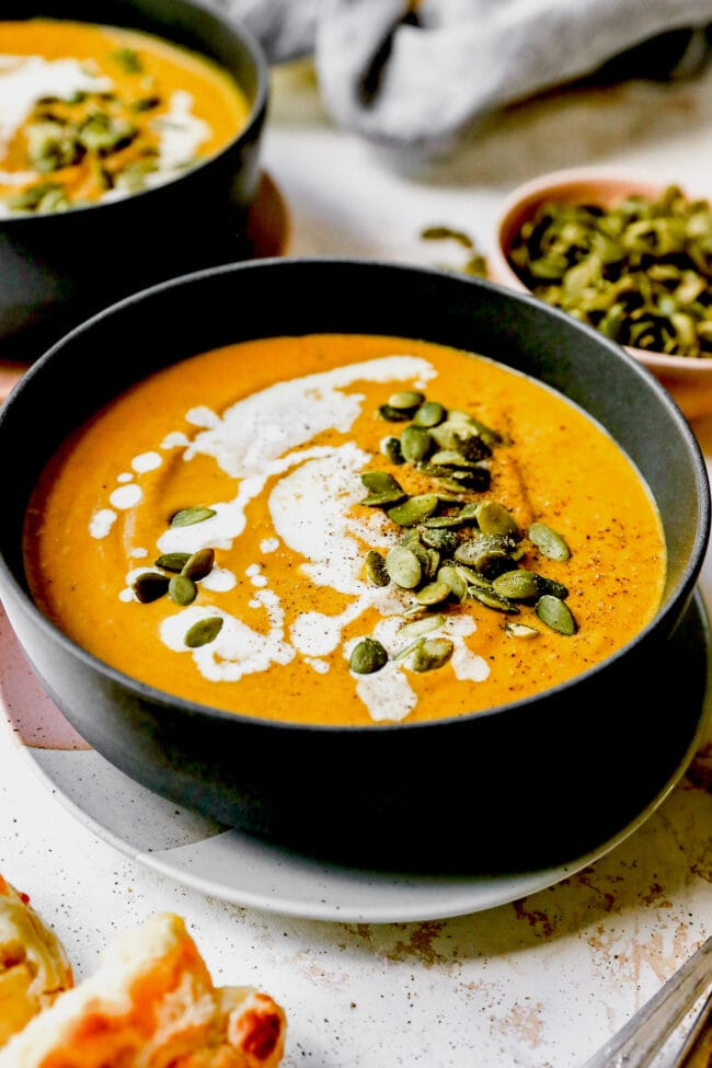 pumpkin soup in bowl with pepitas and cream