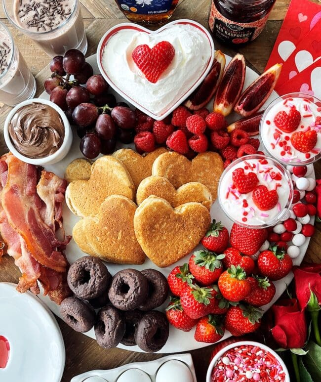 breakfast board with heart pancakes, fruit, and donuts